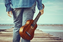 Close Up Of  Hipster Girl Holding Ukulele Guitar Stand Alone On Wooden Bridge Over The Sea, Vintage Tone Effect