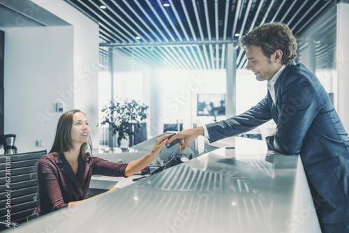 Plakat Uśmiechnięty przystojny mężczyzna w formalnym garniturze jest oparty na blacie i dając swoją kartę debetową czarujący kaukaski kobieta pracuje na recepcji, aby zapłacić rachunki, nowoczesne jasne wnętrze biura lub hotelu