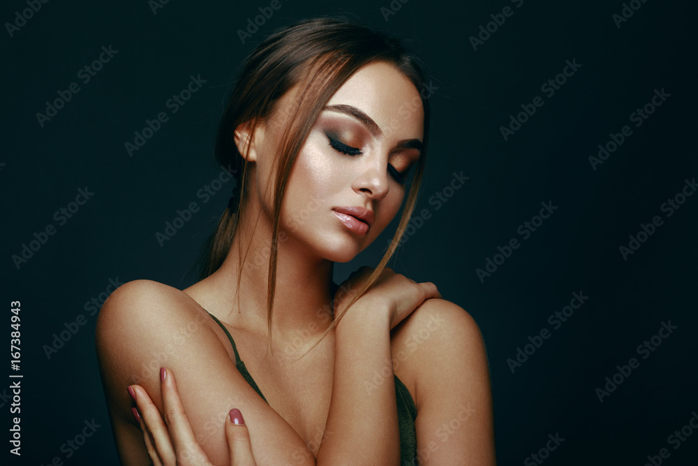 Fototapeta Beauty portrait of a young woman in the studio on a dark background