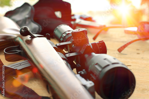 Garden Poster Hunting close up of rifle telescope for sport hunting on table wooden