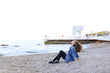 Beautiful young woman relaxes sitting on beach and enjoys view o