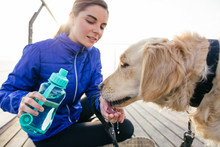 Runner Woman Gives Water To Her Dog After Workout.