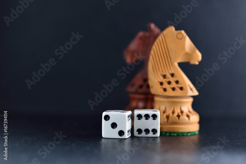 фотография  Two white dice and chess knights ob black