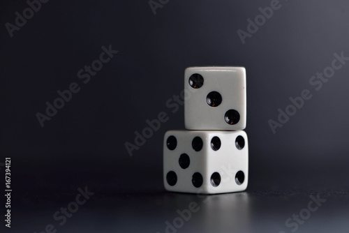 фотография  Two white dice on black