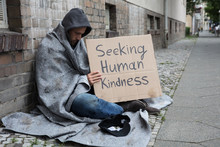 Beggar Showing Seeking Human Kindness Sign On Cardboard
