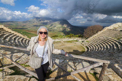 Valokuva  Female tourist taking photo in front of greek theater of Segesta, Sicily, Italy