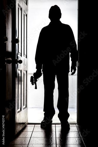Intruder at door, in silhouette with handgun Fototapet