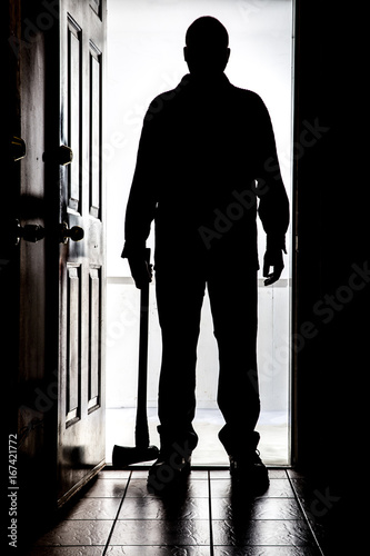 Intruder at door, in silhouette with axe. Canvas Print