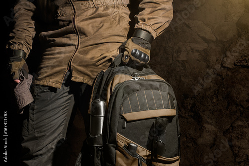 Fotografía  Man in storm jacket and tactical military gloves holding a backpack with travel gear on stone wall background