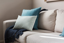 Close Up Of A Fabric Sofa With Styled Cushions And Throw
