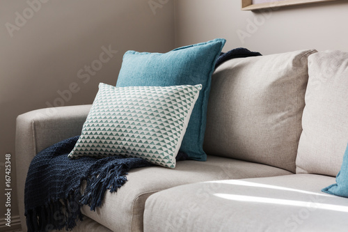 Fotografia Close up of a fabric sofa with styled cushions and throw