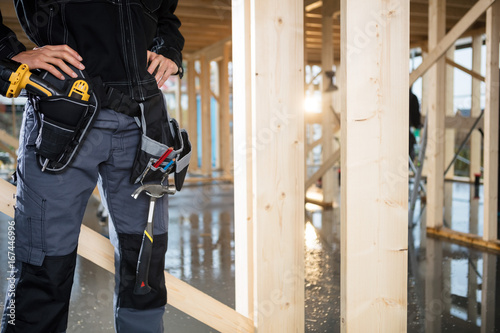 Fototapeta  Midsection Of Carpenter Standing With Hands On Hips At Site