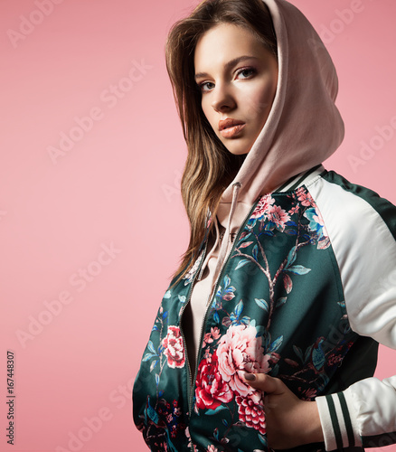 Portrait of a stylish girl in a bomb jacket with floral print standing on a pink background Wall mural