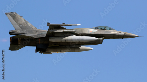 Fototapeta Nowożytny myśliwski samolot w pełnym locie na niebieskim niebie.