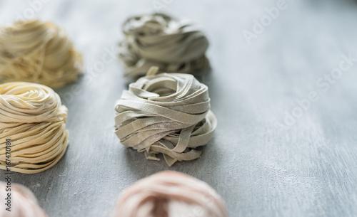 Photo  frische, selbstgemachte Pasta zusammengedreht zu mehreren Nestern auf hellem Unt