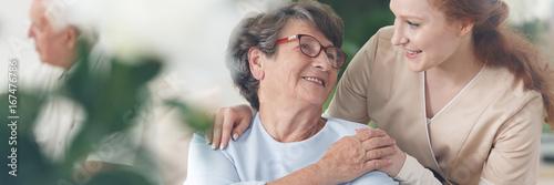 Caregiver comforting smiling senior woman