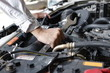 Hands of mechanic with wrench repairing engine of motor car under car hood.