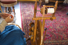 Woman Sitting Using Vintage Loom And Spinning Wheel