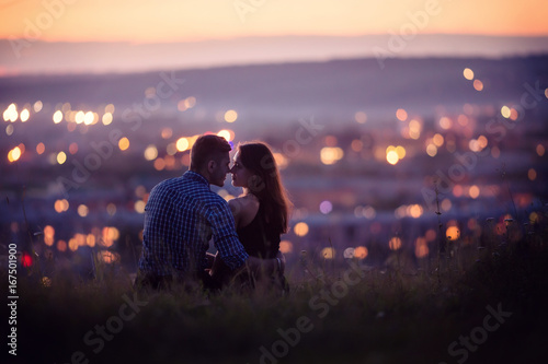 Valokuvatapetti Lovers man and girl against background night city, night starry sky and horizon