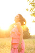 Young woman wearing pink dress at sunset