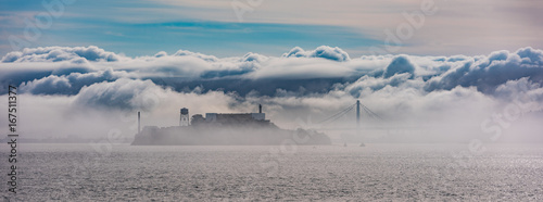 Alcatraz and the Oakland Bay Bridge through the clouds and fog. Wallpaper Mural
