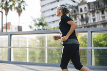 Side View Of Woman Jogging On ...