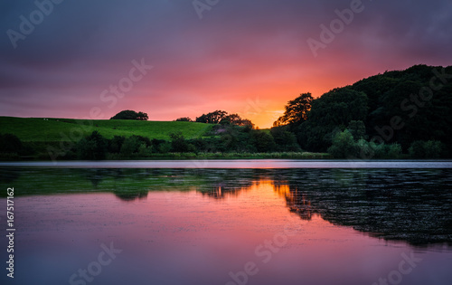 Foto op Aluminium Nachtblauw Vibrant sunset over lake