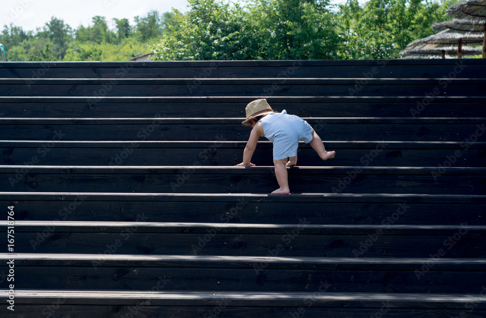 Fototapeta The one-year child climbs up the stairs. Cute baby boy in hat plays on the stairs. The concept of happy childhood. Nature, outdoors, summer