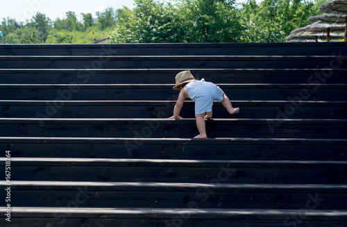 The one-year child climbs up the stairs Fototapeta