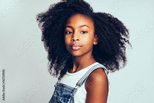 Fotografía  Young African with curly hair standing against a gray background