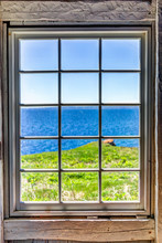 Looking Through Old Window Of House With Cliff And Ocean View In Bonaventure Island, Quebec, Canada