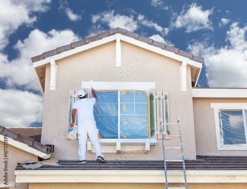 Fototapeta Professional House Painter Painting the Trim And Shutters of A Home. obraz