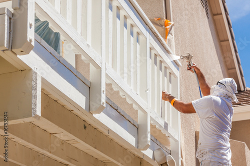 Professional House Painter Wearing Protection Spray Painting Deck Of A Home