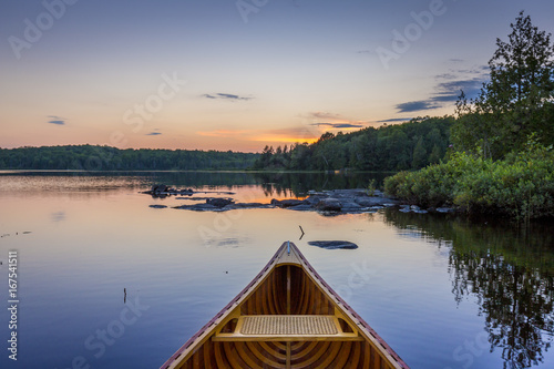 Tableau sur Toile Bow of a cedar canoe on a lake at sunset - Ontario, Canada