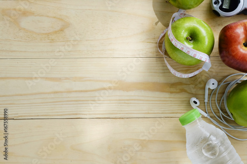 Healthy lifestyle concept. Green and Red Apples,water bottles and stop watch on wooden table copy space for add your text or product.