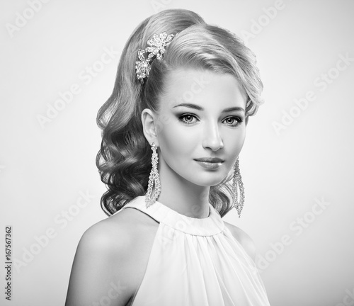 Foto op Canvas womenART Fashion portrait of young beautiful woman with jewelry and elegant hairstyle. Blonde girl with long wavy hair. Perfect make-up. Black and white photo