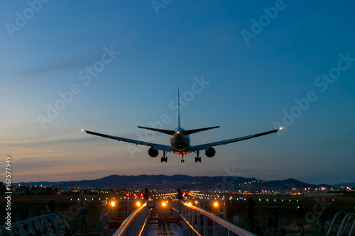 Fotografie, Obraz  夕日と誘導灯に照らされ輝く機体