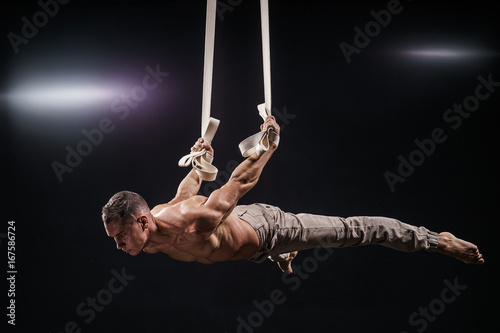Foto op Plexiglas Fitness circus artist on the aerial straps with Strong muscles on black background