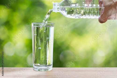 Fototapeta Man's hand holding drinking bottle water and pouring water into glass on wooden table on blurred green nature background with soft sunlight obraz na płótnie