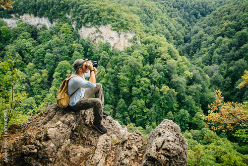 Keuken foto achterwand Olijf Hiker, sitting on top, and examining the forest from above with binoculars. View of the forest from above.