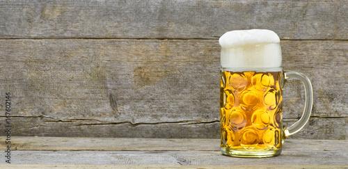 Maßkrug Bier steht auf Holztisch beim Oktoberfest in München, Bayern
