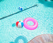 Bright pink float and beach balls in blue swimming pool, floating in refreshing swimming pool with waves reflecting in summer sun. Active vacation background. Lifesaver for kid. Sunny day at the pool