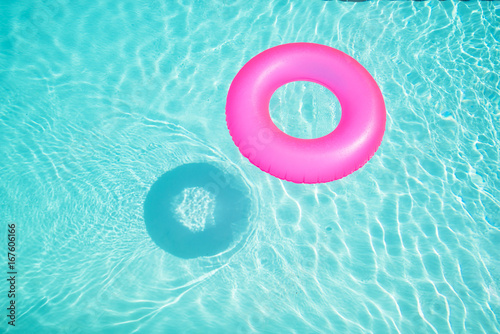 Bright pink float in blue swimming pool, ring floating in a refreshing blue swimming pool with waves reflecting in the summer sun Wallpaper Mural