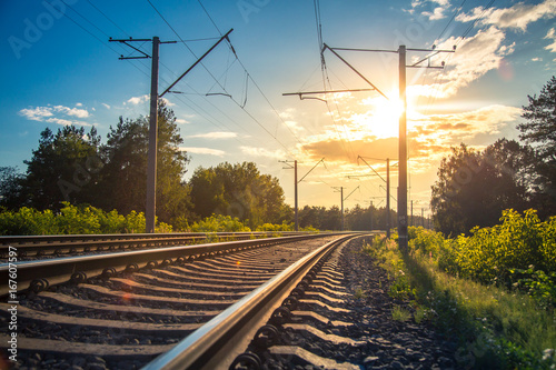 Industrial landscape with rails and railway on sunset.