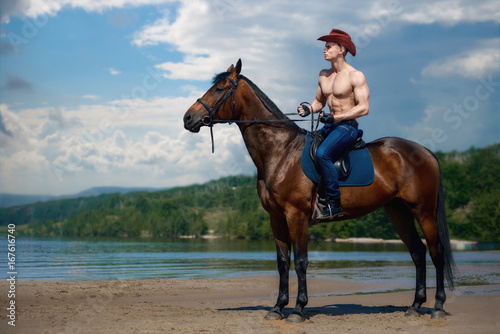 Foto op Aluminium Ontspanning Macho man handsome cowboy riding on a horse on the background of sky and water.