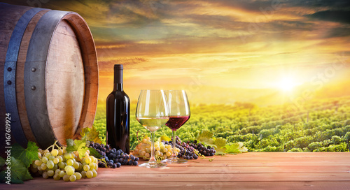 Photo sur Aluminium Vignoble Wine Glasses And Bottle With Barrel In Vineyard At Sunset