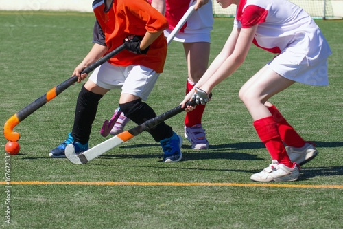 Children playing field hockey competitively. Two defender girls challenging boy attacker