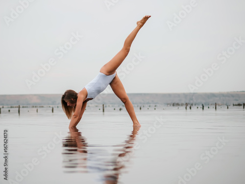Young caucasian woman in swimsuit practicing yoga in water liman, lake or river Canvas Print