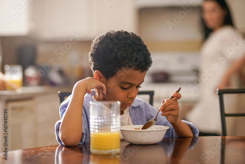 Foto  cute little boy eating breakfast with mother behind him