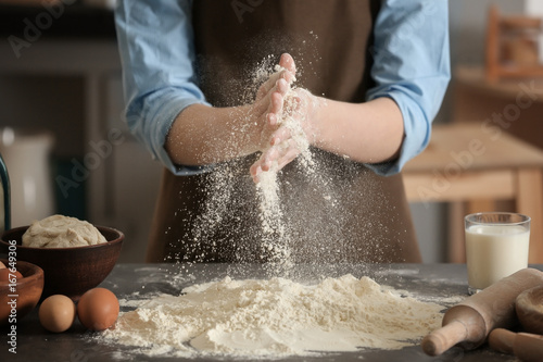 Photographie Female chef with flour and ingredients for dough on table in kitchen